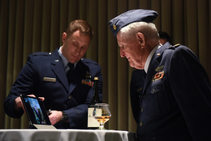 Maj. M. Eugene Johns and Col. Ralph Jenkins, WWII combat aviators and retired Air Force officers with the 510th Fighter Squadron, share a live-streamed greeting during a ceremony to toast their fallen Squadron members, Apr. 7, 2017, at Vandenberg Air Force Base, Calif. Personnel with the 510th FS made a pact that the last two surviving members of the unit who flew combat missions during WWII – Johns and Jenkins – would make a toast from two bottles of brandy which had been saved for the occasion.